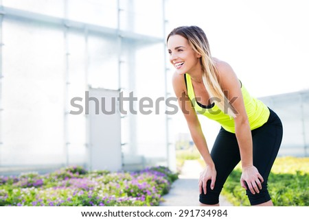 Happy sports woman laughing while having a break in running - stock photo