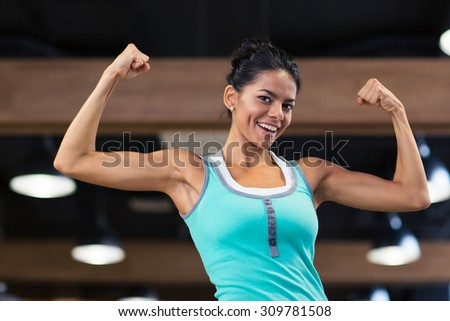 Happy sports woman showing her biceps in gym - stock photo