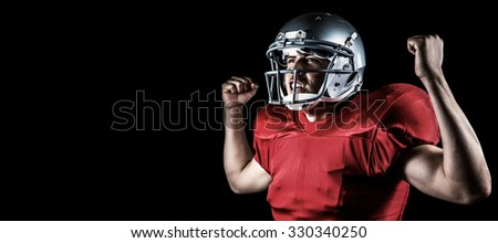 Happy sportsman cheering with clenched fist against black
