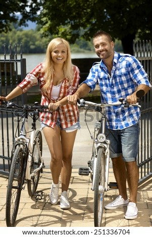 Happy sporty casual couple going for bicycle ride. Attractive blonde woman and handsome stubbly man. Smiling, sport activity, summer. Looking at camera, full size. - stock photo