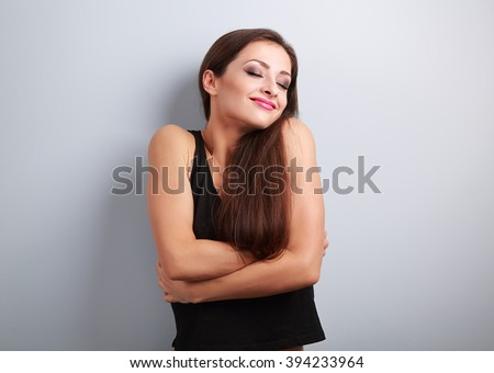 Happy sporty fit woman hugging herself with natural emotional enjoying face. Love concept of yourself  - stock photo