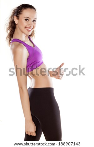 happy sporty girl showing thumbs up on white background