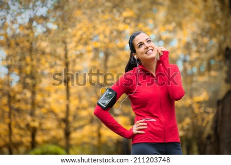 Happy sporty woman wearing smartphone armband and earphones before running in autumn. Female athlete listening music during fitness training outdoor. - stock photo