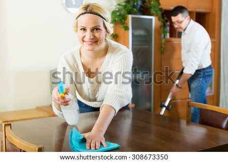Happy spouses dusting and hoovering at domestic interior - stock photo