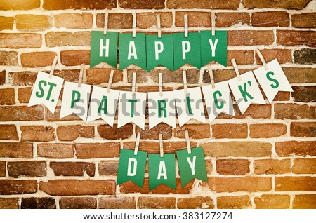 Happy St. Patrick's Day banner lettering on red, old orange brick wall background. Irish national colors greeting postcard template. - stock photo