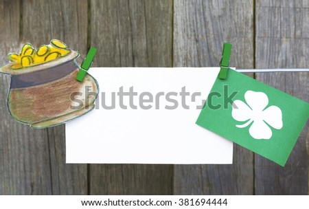 happy St Patrick's Day card, March 17, with Leprechaun hat and pot of gold, on  pegs ( clothespin ) wooden background. space for text - stock photo
