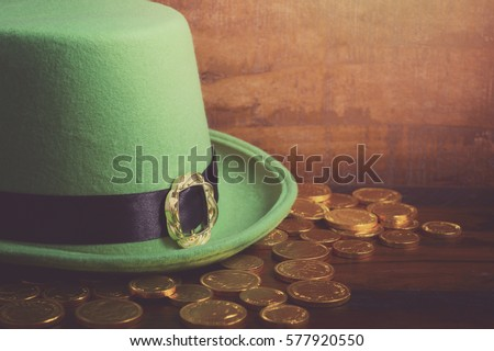 Happy St Patricks Day green leprechaun hat with gold covered chocolate coins on dark wood background, with applied retro style faded filters.