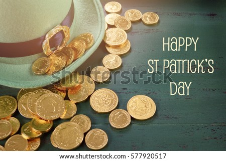 Happy St Patricks Day leprechaun hat with gold chocolate coins on vintage style green wood background with text and applied retro style faded filters.