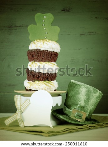Happy St Patricks Day triple layer cupcake with shamrock decorations and leprechaun hat against a vintage style green wood background, with added retro vintage style filters. - stock photo