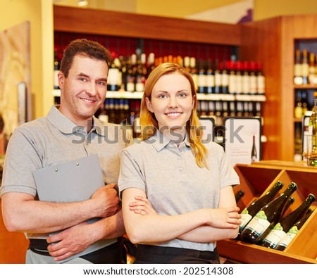 Happy store manager and smiling saleswoman in wine shop - stock photo