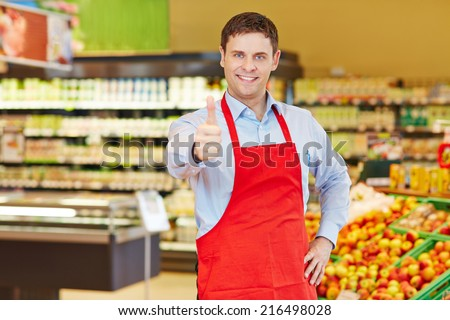 Happy store manager holding his thumbs up in a supermarket - stock photo
