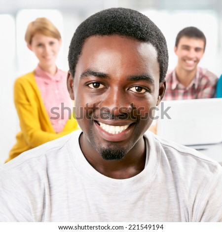 Happy student and his friends on background - stock photo