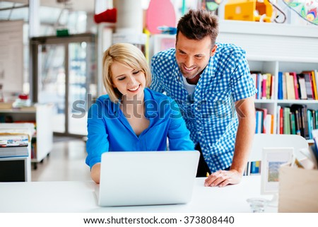 Happy student and teacher learning in library on laptop computer