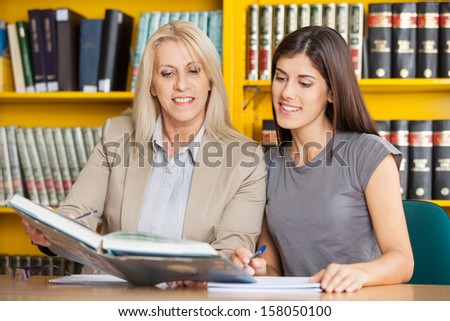 Happy student and teacher reading book together at table in university library - stock photo