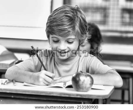 Happy student at elementary school writing on his exercise book. - stock photo