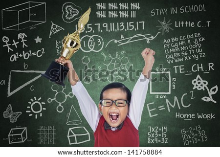 Happy student boy shouting while holding a trophy in classroom - stock photo