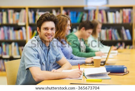 happy student boy with books writing in library - stock photo