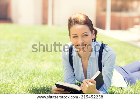 Happy student girl excited to get back to school university. Beautiful woman reading book, laying down on green grass, university campus. Student girl on university college campus park smiling happy. - stock photo