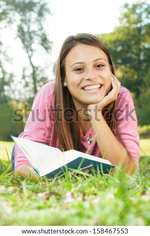 Happy student girl relaxing on green grass reading book.