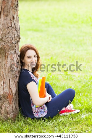 Happy student girl sitting on the grass at the university campus