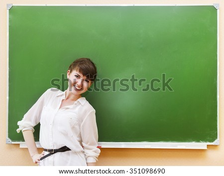Happy student girl standing near clean blackboard in the classroom - stock photo
