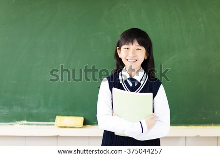 happy student girl with book in classroom