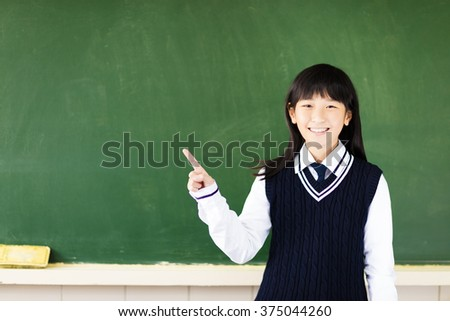 happy student girl with pointing gesture in classroom - stock photo