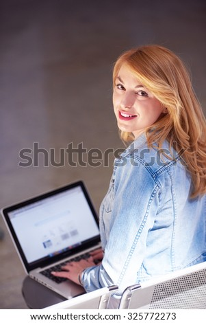 happy student girl working on laptop computer at modern school university indoors