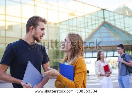 Happy student having conversation next modern college. Education concept