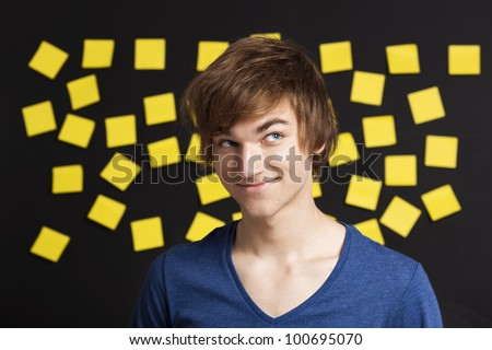 Happy student in front of a board with yellow notes and looking in to the camera - stock photo