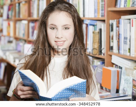 Happy student in the library reading