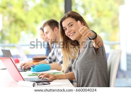 Happy student looking at you with thumbs up in a classroom with classmates in the background