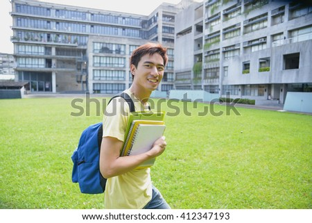 happy student on a grass at a campus