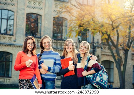 Happy student's life! Group of smiling young women standing together outdoors looking at camera - stock photo
