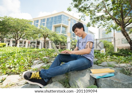 Happy student sitting on the stones and working on laptop on the college campus