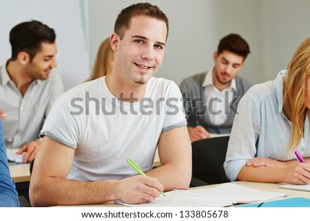 Happy student studying in a course of a college - stock photo