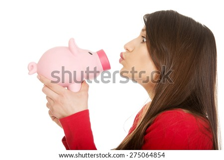 Happy student woman  kissing a piggybank. - stock photo
