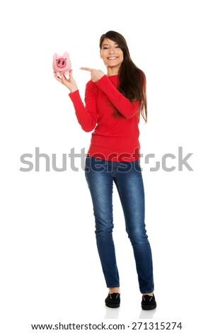 Happy student woman pointing on piggybank. - stock photo