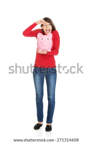 Happy student woman putting a coin to piggybank. - stock photo