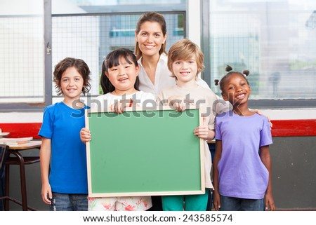 Happy students and teacher  holding empty chalkboard. Primary school interracial concept. - stock photo