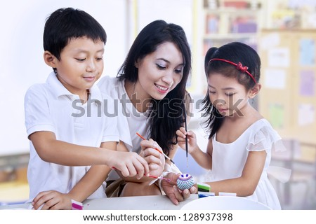 Happy students and teacher painting easter eggs - stock photo