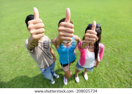 happy students in campus showing sign ok thumb, asian - stock photo