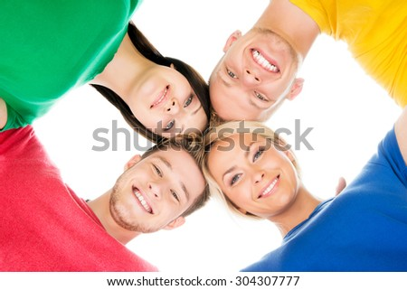 Happy students in colorful clothing standing together touching heads