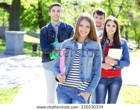 Happy students in park - stock photo