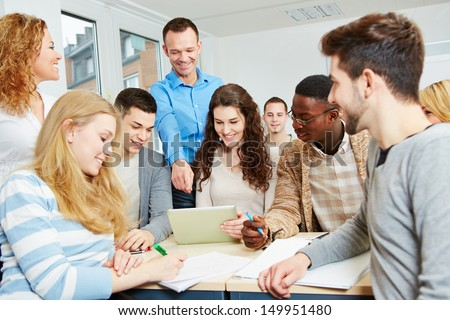 Happy students learning with teacher in university class - stock photo
