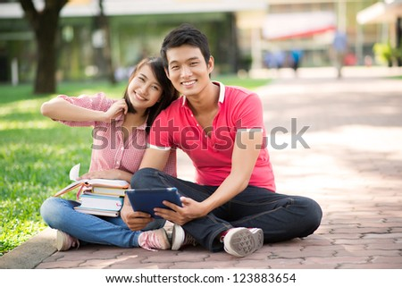 Happy students sitting comfortably on a campus pathway - stock photo