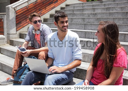 Happy students sitting on stairs using digital tablet and conservation to each other in school, caucasian