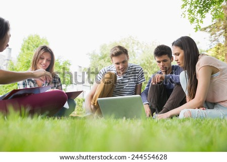 Happy students sitting outside on campus at the university - stock photo