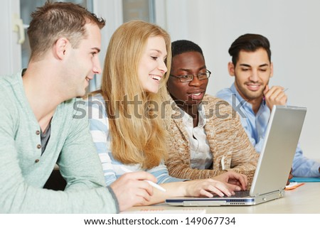 Happy students taking private lessons online with laptop computer - stock photo
