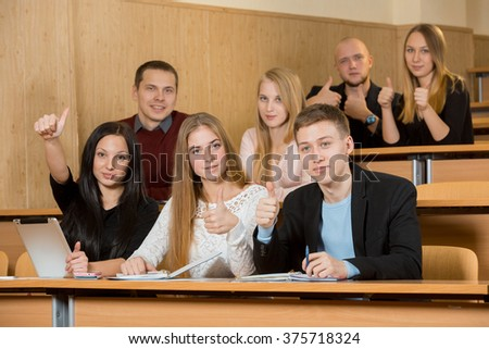 Happy students thumbs up and smiling in college classroom